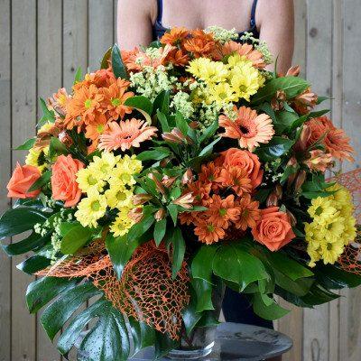 Jarrón de flor variada tonos naranjas