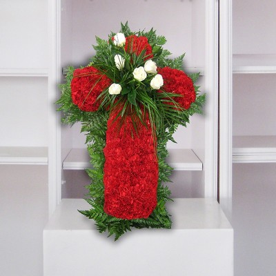 Creu de clavells vermells i flor blanca