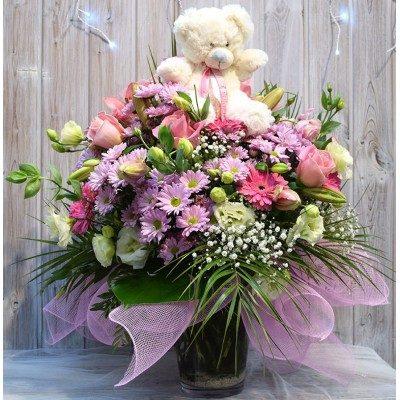 Jarrón de flor variada niña con peluche